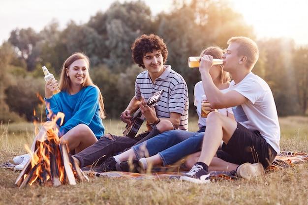 Menschen, picknick und lifestyle-konzept. freudige vier freunde singen lied und spielen gitarre, sitzen am lagerfeuer, genießen sommergetränk, atmen frische luft