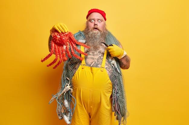 Menschen plötzliches reaktionskonzept. bärtiger übergewichtiger männlicher seemann hält große rote tintenfische starrt mit stupor