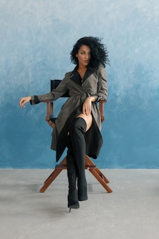 Menschen, rasse, ethnizität und modekonzept - schwarzes schönheitsmodell, das in hohen stiefeln posiert. junge hübsche schöne mulattin, die im regiestuhl beim film sitzt. frau im grauen regenmantel, afrofrisur