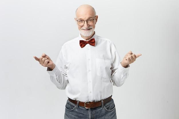 Menschen, reifes alter, ruhestand und weisheitskonzept. bild des schönen fröhlichen älteren europäischen mannes mit dem dicken grauen bart, der zeigefinger in entgegengesetzte richtungen zeigt und spielerisch lächelt