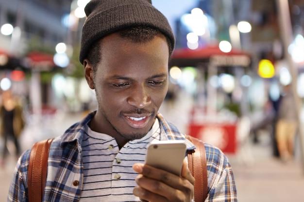Menschen, reisen, lifestyle und moderne technologie. kopfschuss eines positiven jungen afroamerikanischen rucksacktouristen, der die online-navigations-app auf seinem smartphone verwendet, während er abends durch eine fremde stadt läuft