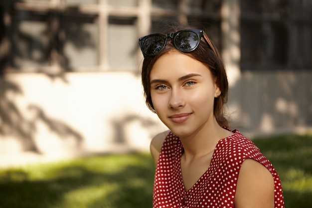 Menschen, ruhe, schönheit, stil und modekonzept. porträt der niedlichen charmanten kaukasischen jungen frau mit schatten auf ihrem kopf, die schönen sommertag im freien genießen