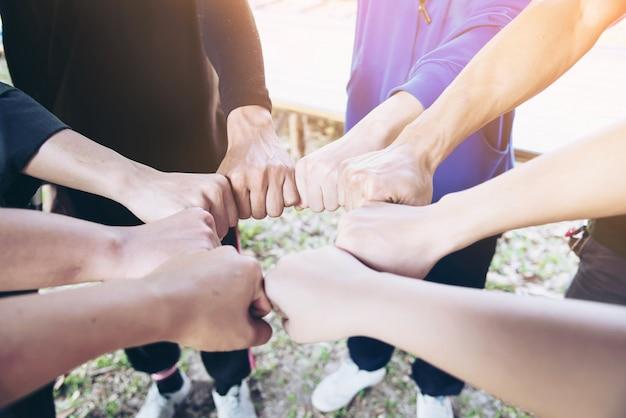 Menschen schließen sich hand während ihrer arbeit - menschliches verpflichtungskonzept an