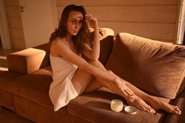 Menschen schönheit depilation epilation körperpflege konzept schöne frau nackte beine sitzen auf der couch bei