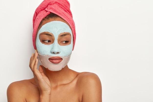 Menschen, schönheit, selbstpflegekonzept. nachdenkliche dunkelhäutige frau berührt wange, trägt tonmaske und kollagenpflaster um die lippen auf, trägt handtuch auf dem kopf