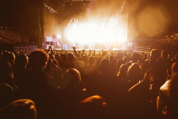 Menschen silhouetten beim musikkonzert. menge und fans, die auf dem festival die rockband lieben