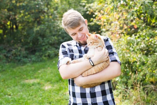 Menschen, sommer, tourismus und naturkonzept - mann, der katze hält.