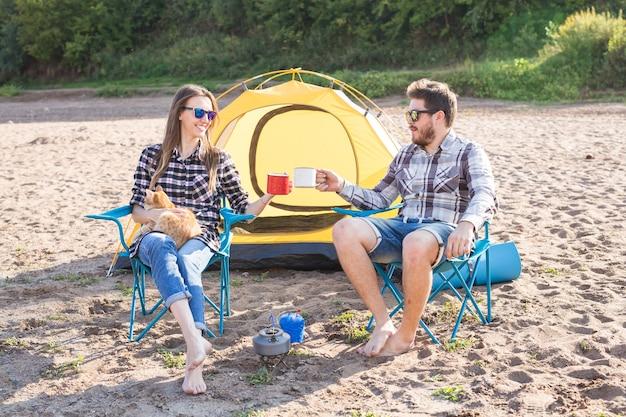Menschen, sommertourismus und naturkonzept - junges paar, das tee nahe zelt trinkt.