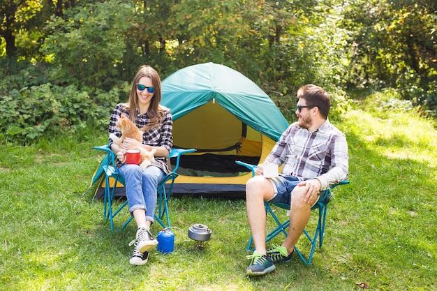 Menschen, sommertourismus und naturkonzept - junges paar sitzt in der nähe eines zeltes