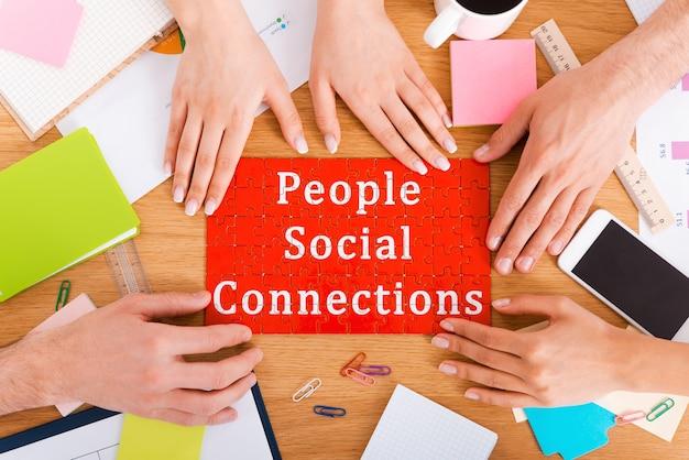 Menschen soziale verbindungen. draufsicht nahaufnahme von menschen, die puzzle mit sozialem verbindungstext berühren
