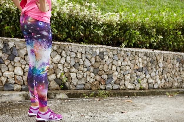Menschen, sport und entschlossenheit. beschnittenes porträt einer läuferin, die leggings mit weltraumdruck und stilvolle laufschuhe trägt, auf dem bürgersteig steht, die hände auf ihrer taille hält und sich auf den lauf vorbereitet