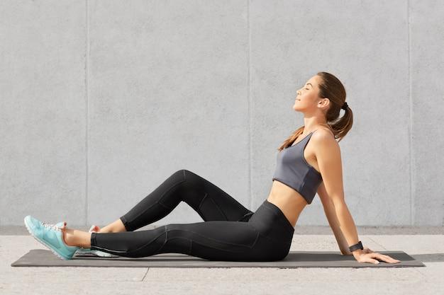 Menschen-, sport- und entspannungskonzept. entspannte fitnessfrau mit perfekter figur sitzt auf trainingsmatte, hält die augen geschlossen