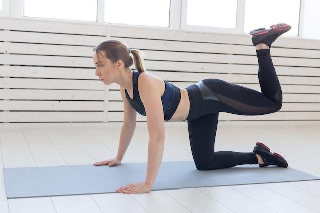 Menschen-, sport- und fitnesskonzept - schlanke junge frau in der sportbekleidung, die eselkickübung macht