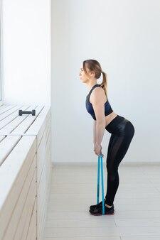Menschen-, sport- und fitnesskonzept - training der jungen frau mit trainingsband im fitnessstudio.