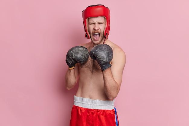 Menschen sport und gesunde lebensweise konzept. emotionaler männlicher boxer schreit wütend und trägt schützende kopfbedeckungs-boxhandschuhe und kampfbereite shorts