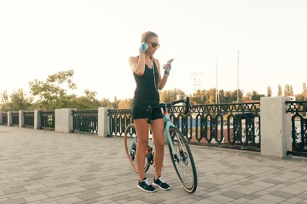 Menschen-, sport- und lebensstilkonzept - schönes mädchen, das in einem warmen tag natur mit einem fahrrad, einem telefon und kopfhörern geht, hübsches süßes mädchen, das smartphone neben ihrem fahrrad in parkpalmen an einem sonnigen tag verwendet