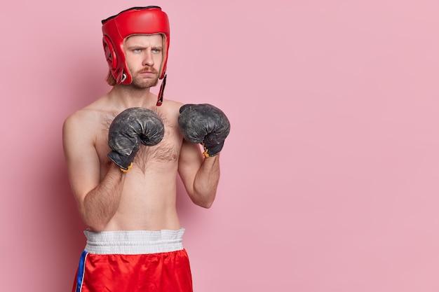 Menschen sportstärke und motivationskonzept. der horizontale schuss eines ernsthaften männlichen boxers, der bereit für den kampf ist, runzelt die stirn und ist ein strenger trainer, der die ausdauer des trainings zeigt
