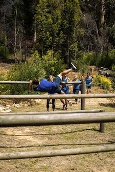 Menschen springen über die hürden während des hindernislaufs