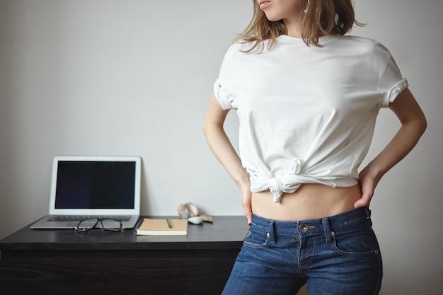 Menschen, stil, mode, kleidung und designkonzept. schöne stilvolle junge frau mit schlankem schlanken körper, der drinnen mit laptop im hintergrund aufwirft, weißes t-shirt mit copyspace für ihr logo tragend