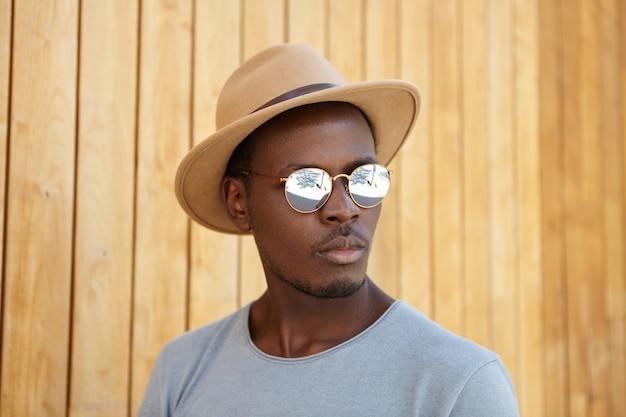 Menschen, stil und modekonzept. modisch aussehendes modisches junges afroamerikanisches männliches modell, das spiegelsonnenbrille und kopfschmuck trägt, der an holzwand mit kopienraum für ihre information aufwirft