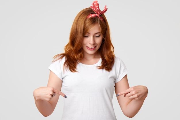 Menschen, stil, werbung, kleidungskonzept. erfreute schöne weibliche punkte am weißen t-shirt mit kopienplatz für ihr logo oder ihre werbung, freut sich über den neukauf, isoliert auf weiß