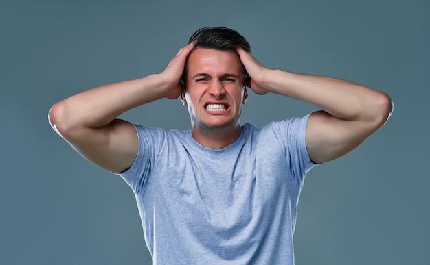 Menschen, stress, anspannung und migräne-konzept. verärgerter unglücklicher junger mann, der den kopf mit den händen drückt und an kopfschmerzen leidet