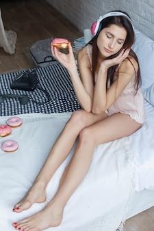 Menschen, süßigkeiten und fast-food-konzept - glückliche junge frau oder jugendliches mädchen, die donut isst und im bett kniet. schönes schlankes sexy mädchen liegt im bett mit süßen donuts, frühstückszeit, guten morgen-konzept