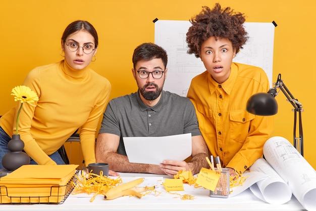 Menschen teamwork und zusammenarbeit konzept. drei schockierte kollegen arbeiten zusammen, um einen architekturplan zu erstellen, starren überrascht, posieren bei der arbeit am schreibtisch am bauprojekt.