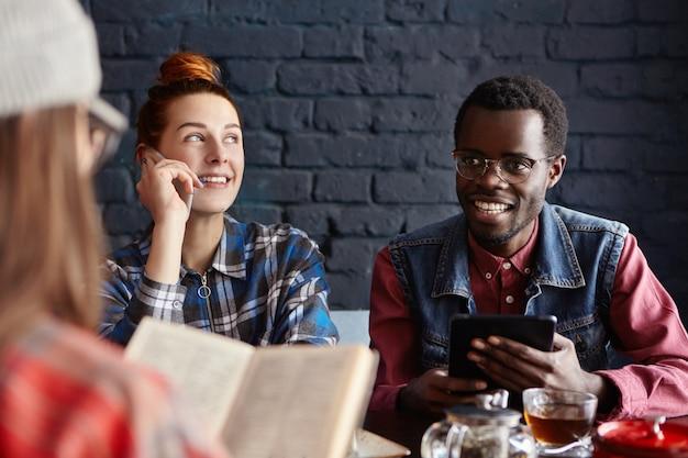 Menschen, technologie und kommunikation. gruppe von drei jungen leuten, die gespräch im café haben: rothaarige frau, die auf handy spricht, afrikanischer mann, der elektronisches tablett verwendet