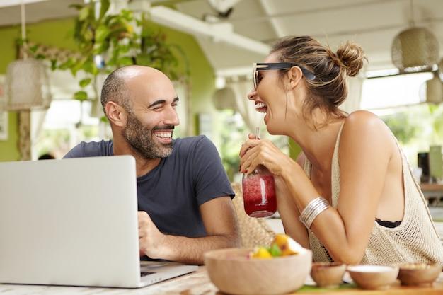 Menschen-, technologie- und lifestyle-konzept. attraktiver kahlköpfiger mann mit bart, der vor laptop sitzt und seiner freundin mit smoothie in ihren händen witze erzählt.