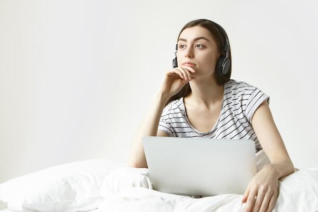 Menschen, technologie und modernes lifestyle-konzept. schöne junge brünette frau, die auf weißer bettwäsche mit offenem tragbarem computer auf ihrem schoß sitzt und kopfhörer verwendet, während online-hörbuch hört