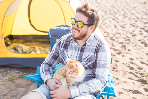 Menschen, tourismus und naturkonzept - mann, der katze auf natur hält