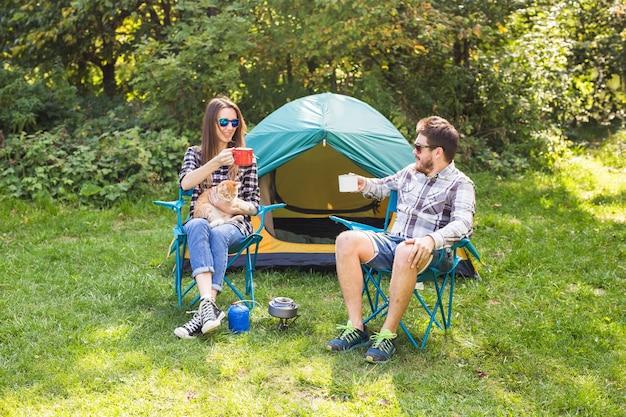 Menschen-, tourismus- und naturkonzept - paar, das spaß auf campingausflug hat und mit katze spielt.