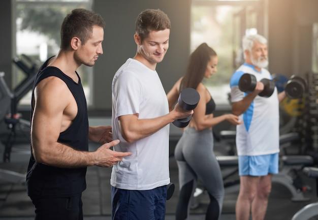 Menschen trainieren im fitnessstudio mit personal trainer.