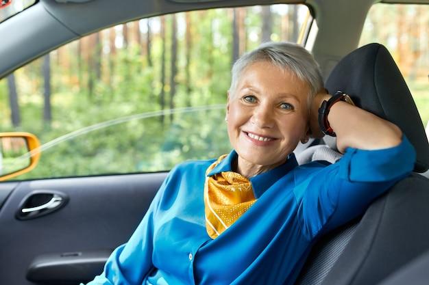 Menschen-, transport-, reise- und freizeitkonzept. porträt einer schönen eleganten frau mittleren alters, die bequem auf dem beifahrersitz sitzt