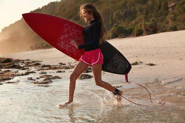 Menschen- und abenteuerkonzept. aktiver mutiger surfboarder läuft schnell als große welle bemerkt, will es treffen