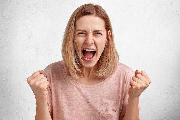 Menschen- und aggressionskonzept. gereiztes junges weibliches model mit geschwungener frisur, gekleidet in freizeitkleidung, geballte fäuste vor wut, hat streit mit ehemann
