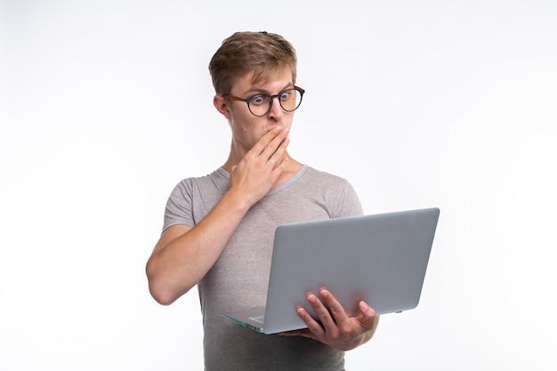 Menschen und bildungskonzept. entsetzter mann, der einen laptop hält.