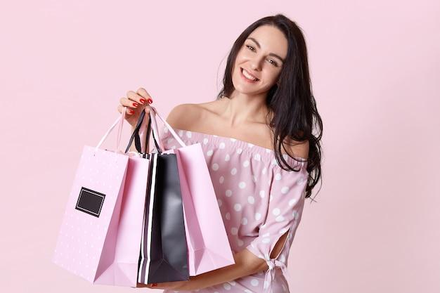 Menschen und einkaufskonzept. glückliche dunkelhaarige frau shopaholic gekleidet im gepunkteten kleid, trägt einkaufstaschen, isoliert auf rosa, hat rote maniküre. kundin steht drinnen