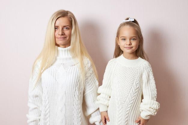 Menschen- und generationenkonzept. isolierte aufnahme der attraktiven jungen europäischen mutter, die händchen haltend mit der schönen kleinen tochter aufwirft, beide gekleidet in kuschelige warme pullover