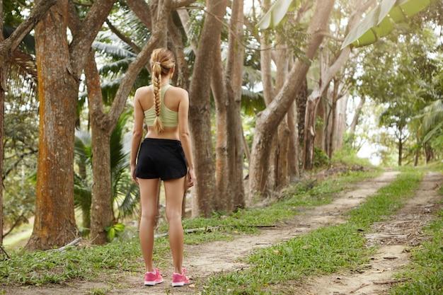 Menschen und gesunder lebensstil konzept. schönes passendes mädchen mit zopf, das laufendes outfit trägt, das nach der trainingseinheit steht, die auf spur im wald steht.