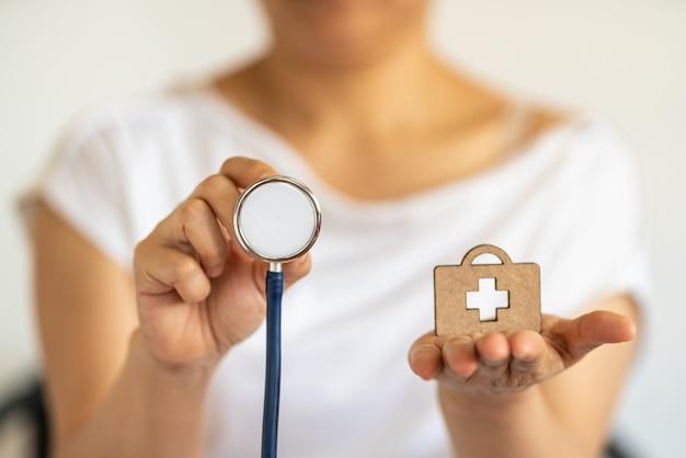 Menschen- und gesundheitskonzept. nahaufnahme der frauenhand, die stethoskop mit hölzerner gestanzter tasche mit medizinischem kreuzlogo hält.