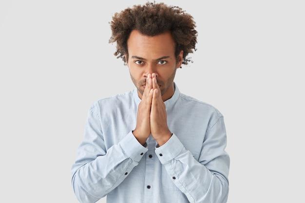 Menschen- und glaubenskonzept. der hübsche junge, ernsthafte afroamerikaner hält die hände in der gebetsgeste, sieht selbstbewusst aus, trägt ein weißes hemd und glaubt fest daran, dass seine träume wahr werden.