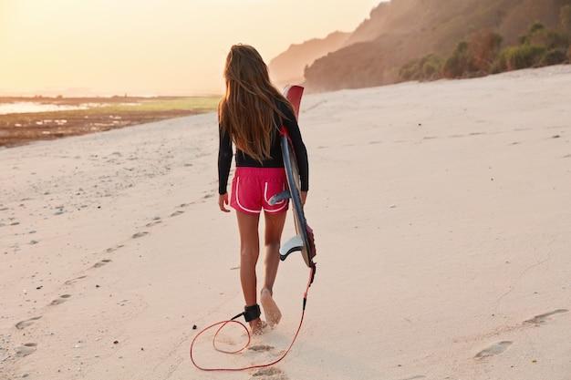 Menschen- und hobbykonzept. rückansicht der schlanken langhaarigen jungen frau in den rosa shorts und im schwarzen rollkragenpullover