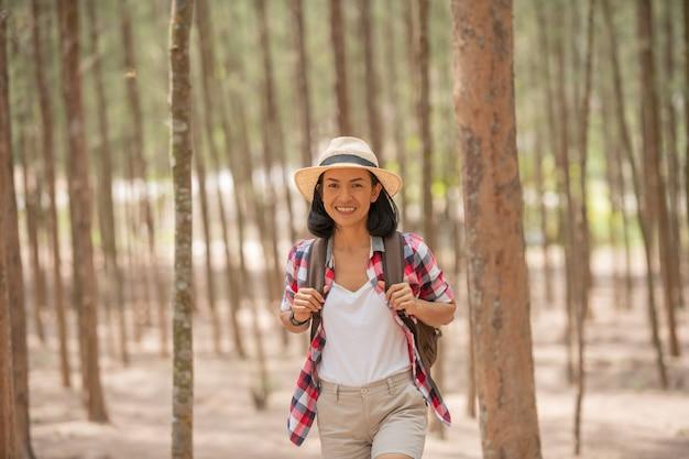 Menschen und lebensstile abenteuer, reisen, tourismus, wanderung und menschenkonzept - reisende frauen, die im wald des lächelnden gehens mit rucksack, hut im wald gehen.