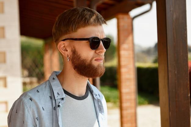 Menschen- und lifestyle-konzept. attraktiver junger kaukasischer mann mit langem roten bart, der schwarze sonnenbrille trägt