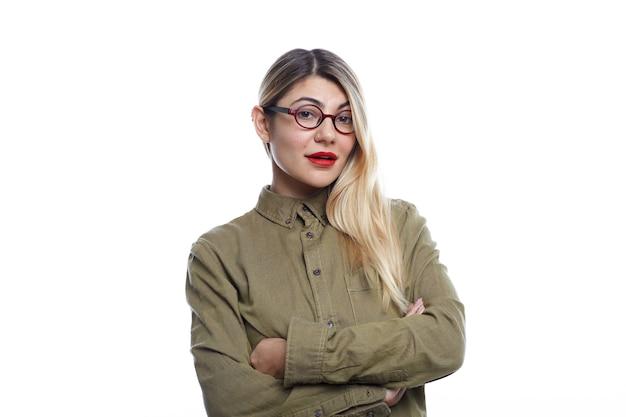 Menschen- und lifestyle-konzept. horizontale aufnahme der schönen jungen blonden frau des kaukasischen aussehens, die modische brillen und grünes jeanshemd trägt, das mit verschränkten armen aufwirft