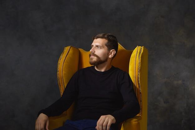 Menschen- und lifestyle-konzept. horizontaler schuss des gutaussehenden kaukasischen bärtigen kerls in seinen dreißigern, der sich im haus ausruht, im sessel sitzt, sich nach der arbeit entspannt, müden gesichtsausdruck hat