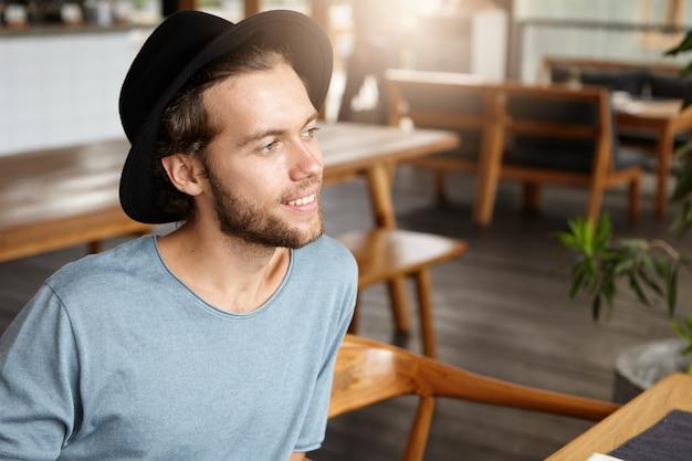 Menschen- und lifestyle-konzept. porträt des hübschen jungen bärtigen mannes im schwarzen hut und im lässigen t-shirt, das vor ihm mit niedlichem lächeln schaut, während am kaffeehaus am sonnigen tag sitzt
