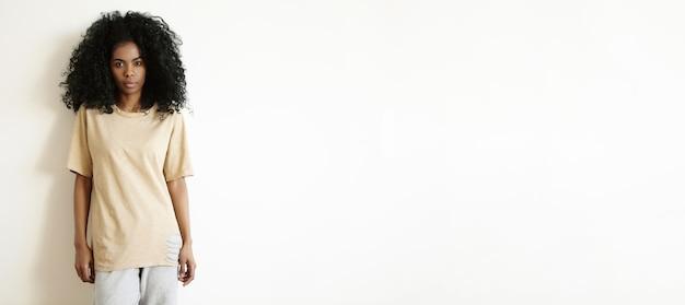 Menschen- und lifestyle-konzept. schöne junge dunkelhäutige frau, die lässig gekleidet ist und drinnen ruhe hat, an einer leeren weißen wand steht und mit ernstem ausdruck auf ihrem gesicht schaut
